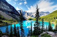 <p>Tall alpine trees surround the turquoise waters of Lake Louise in Alberta, Canada.</p>