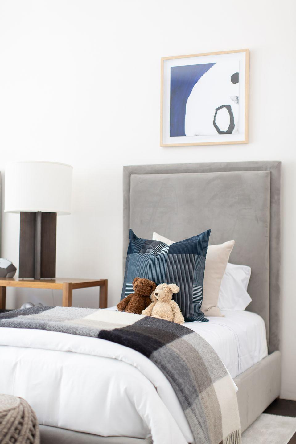 """<p>From the gray suede bed frame and industrial table lamp to the plaid throws and graphic framed print, decorator <a href=""""https://breeganjane.com/"""" rel=""""nofollow noopener"""" target=""""_blank"""" data-ylk=""""slk:Breegan Jane"""" class=""""link rapid-noclick-resp"""">Breegan Jane</a> chose understated and cozy staples for a versatile foundation that the child can build off of for years to come. </p>"""