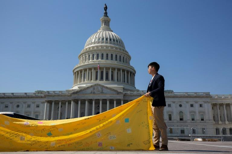 Hong Kong pro-democracy activist Joshua Wong, outside the US Capitol in Washington, unfurls a banner supporting US legislation aimed at defending civil rights in the semi-autonomous city