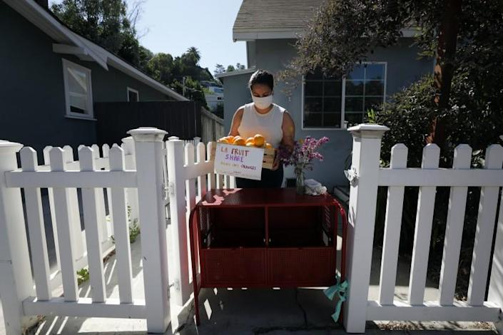 """Vreny Palacios sets out a box of oranges to share. Angelenos registered online to put fruit in front of their homes to share with the community. <span class=""""copyright"""">(Myung J. Chun / Los Angeles Times)</span>"""