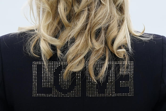 """First lady Jill Biden turns around to show the word """"love"""" on the back of her jacket as she speaks with reporters after visiting with Carrie Johnson, wife of British Prime Minister Boris Johnson, ahead of the G-7 summit, Thursday, June 10, 2021, in Carbis Bay, England. (AP Photo/Patrick Semansky)"""