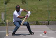 Ali Cheema, a former cricketer from Pakistan, plays a shot during a game of cricket played by migrants in Tuzla, Bosnia, Friday, May 21, 2021. Cheema, who said he started playing cricket when he was 7 and used to play for several clubs in his native Pakistan. Now 24, Cheema has been in Bosnia for the past two years. The Rome-based Baobab Experience group brought cricket equipment for the migrants in the Bosnian capital of Sarajevo and the central town of Tuzla, offering a rare opportunity for relaxation and fun for the people who spend months, if not years, stuck in camps while fleeing war and poverty in their nations and chasing their dreams of a better future. (AP Photo/Kemal Softic)