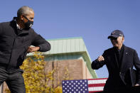 Democratic presidential candidate former Vice President Joe Biden, right, and former President Barack Obama greet each other with an air elbow bump, at the conclusion of rally at Northwestern High School in Flint, Mich., Saturday, Oct. 31, 2020. (AP Photo/Andrew Harnik)