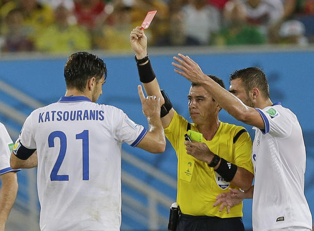 Referee Joel Aguilar from El Salvador shows a red card to Greece's Kostas Katsouranis, left, during the group C World Cup soccer match between Japan and Greece at the Arena das Dunas in Natal, Brazil, Thursday, June 19, 2014. (AP Photo/Ricardo Mazalan)