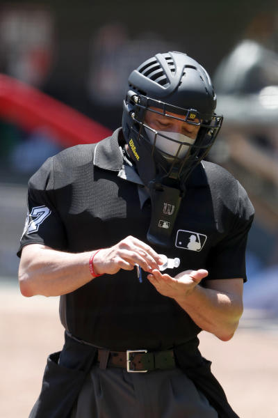 FILE - In this July 16, 2020, file photo, umpire Carlos Torres (37) sanitizes his hands between batters during an Atlanta Braves intrasquad baseball game in Atlanta. Public health experts have mixed feelings about baseball's hopes to open its season July 23. The field of play — even the batter's box — should be fairly safe, except perhaps for the catcher and plate umpire. (AP Photo/John Bazemore, File)
