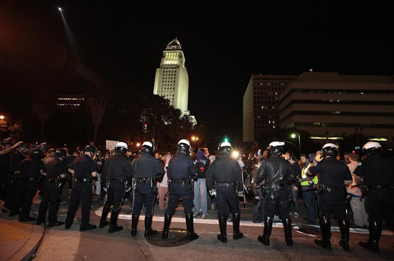 Los Angeles police officers Face protesters from the Occupy LA encampment outside City Hall in Los Angeles Wednesday Nov. 30, 2011. Police have moved in on the Occupy Los Angeles encampment and began arresting protesters who defied an eviction notice.   (AP Photo/Lucy Nicholson/Pool)