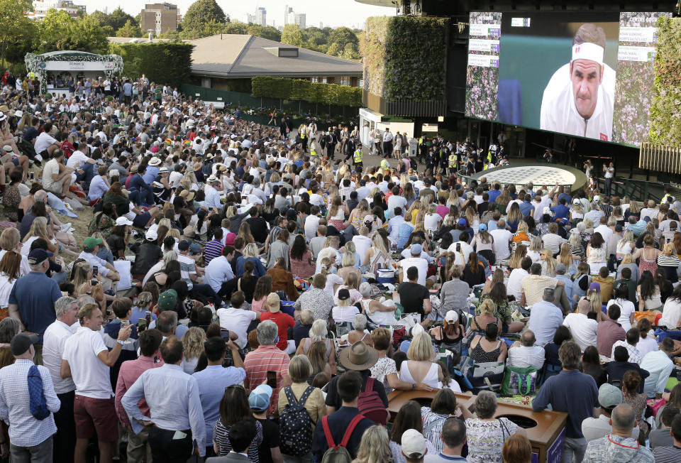 FILE - In this Friday, July 12, 2019 file photo, people sitting on Murray mound watch the men's singles semifinal match between Spain's Rafael Nadal and Switzerland's Roger Federer on day eleven of the Wimbledon Tennis Championships in London. For all of the pandemic-related planning discussed for this year's return of Wimbledon — much still to be determined, including fan capacity and prize money , Tuesday's biggest news out of the All England Club takes effect in 2022: There will be play on the Grand Slam tournament's middle Sunday. (AP Photo/Tim Ireland, File)