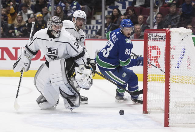 Los Angeles Kings goalie Jonathan Quick (32) and teammate Anze Kopitar (11), of Slovenia, and Vancouver Canucks' Jay Beagle (83) watch as the puck bounces off the posts and stays out of the goal during the second period of an NHL hockey game Wednesday, Oct. 9, 2019, in Vancouver, British Columbia. (Darryl Dyck/The Canadian Press via AP)