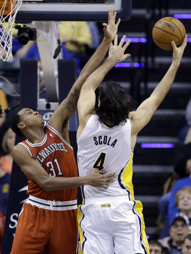 Indiana Pacers forward Luis Scola, right, shoots over Milwaukee Bucks forward John Henson in the first half of an NBA basketball game in Indianapolis, Friday, Nov. 15, 2013. (AP Photo/Michael Conroy)