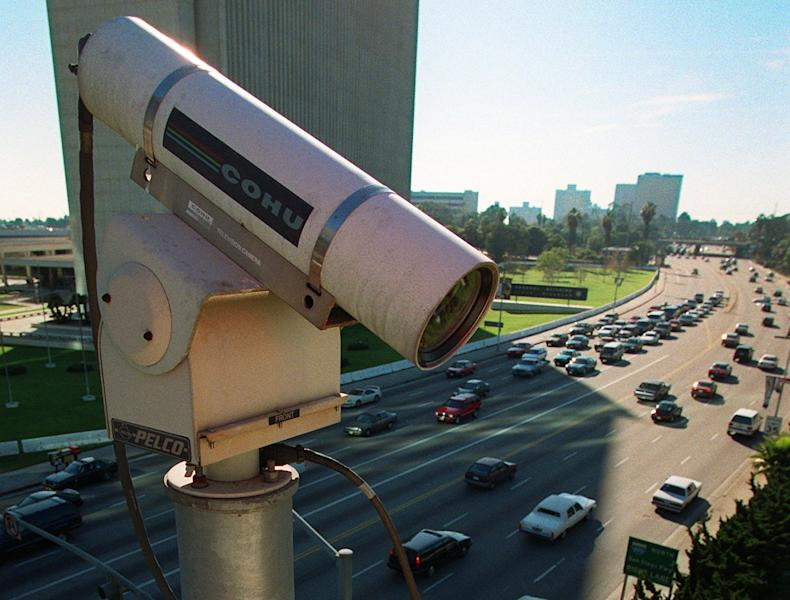 File - This Jan. 8, 1997 file photo shows a remote camera for the Los Angeles Department of Transportation oversees the traffic flow on the corner of Wilshire and Veteran in the Westwood area of Los Angeles. In small towns and big cities, police and politicians are pointing to the surveillance video that was key to identifying the Boston Marathon bombing suspects as a reason to bolster their own networks and get more electronic eyes on their streets. In Los Angeles, a councilman wants police to broaden their network by giving them access to traffic cameras used to monitor the flow of cars on the road. (AP Photo/Michael Caulfield,File)