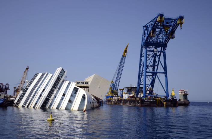 FILE - In this Monday, July 15, 2013 file photo, the Costa Concordia ship wreck lies on its side in the Tuscan Island of Isola del Giglio, Italy. An Italian court on Saturday, July 20, 2013 accepted plea bargains for five Costa Crociere employees in the Costa Concordia shipwreck that killed 32 crew and passengers, convicting all of multiple manslaughter and negligence. The sentences were all under three years. The highest went to the crisis coordinator for the cruise company, who was sentenced to two years and 10 months. The ship's hotel director was sentenced to two years and six months while two bridge officers and a helmsman got sentences ranging from one year and eight months to one year and 11 months. The plea bargains were handled separately from the trial of Costa Concordia Capt. Francesco Schettino, who is charged with manslaughter for causing the January 2012 shipwreck off the Tuscan island of Giglio and abandoning the vessel with thousands aboard. (AP Photo/ Michele Barbero, Files)