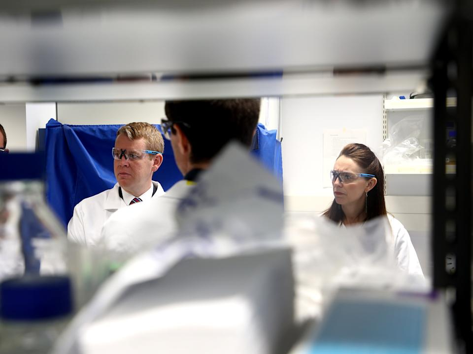 Jacinda Ardern and Covid-19 response minister Chris Hipkins visit a lab at Auckland University after announcing they have secured enough vaccine doses to immunise the whole population (Getty Images)