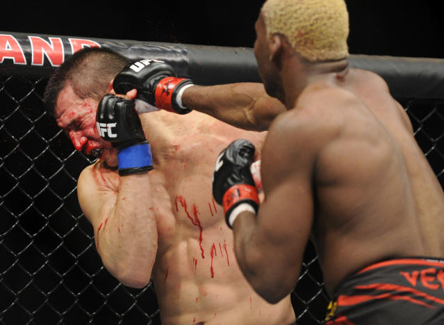 Bobby Voelker, left, is punched by William Macario during a UFC 168 mixed martial arts welterweight bout on Saturday, Dec. 28, 2013, in Las Vegas. Macario won by unanimous decision. (AP Photo/David Becker)