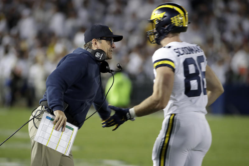 Michigan head coach Jim Harbaugh, left, greets tight end Luke Schoonmaker (86) as he returns to the sidelines during the first half of an NCAA college football game against Penn State in State College, Pa., Saturday, Oct. 19, 2019. (AP Photo/Gene J. Puskar)