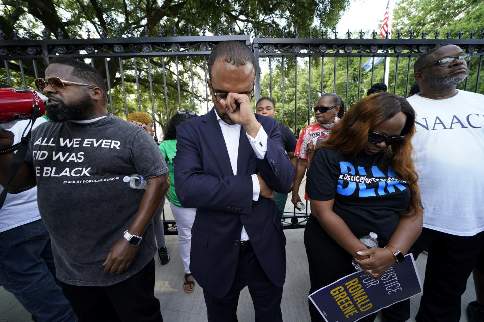 Ron Haley, center, attorney for the family of Ronald Greene, bows his head in prayer outside the gates of the governor's mansion in Baton Rouge, La., Thursday, May 27, 2021, after a march from the state Capitol, protesting the death of Greene, who died in the custody of Louisiana State Police in 2019. (AP Photo/Gerald Herbert)