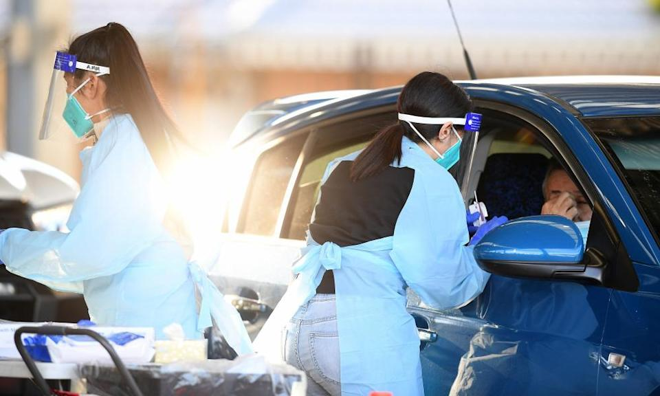 Health workers administer Covid tests at a drive-through testing clinic at Fairfield in Sydney.