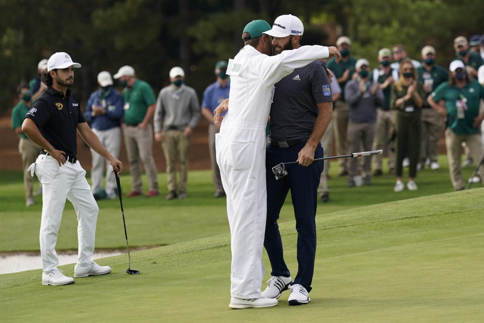 Dustin Johnson is hugged by his caddie Austin Johnson after winning the Masters golf tournament Sunday, Nov. 15, 2020, in Augusta, Ga. (AP Photo/David J. Phillip)