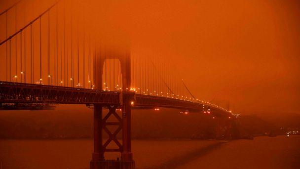 PHOTO: Cars drive along the Golden Gate Bridge under an orange smoke filled sky at midday in San Francisco, Sept. 9, 2020. (Harold Postic/AFP via Getty Images)