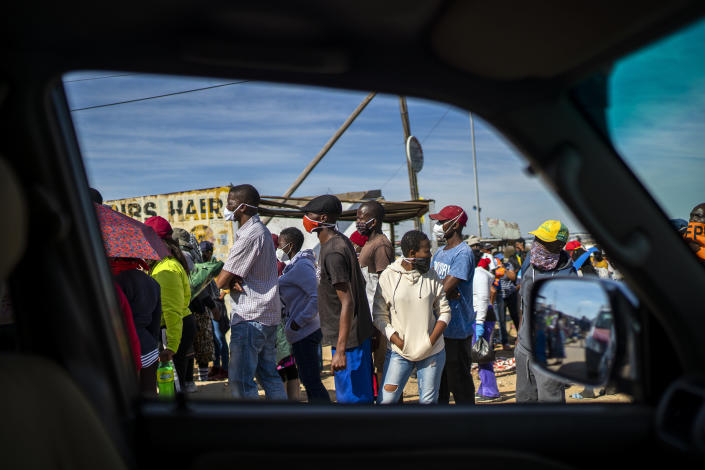 People line up to receive food handouts in the Olievenhoutbos township of Midrand, South Africa, Saturday May 2, 2020. though South Africa begun a phased easing of its strict lockdown measures on May 1, its confirmed cases of coronavirus continue to increase. (AP Photo/Jerome Delay)