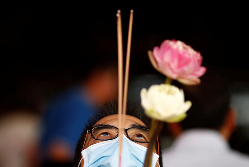 A man wearing a mask in precaution of the coronavirus outbreak prays at the Kwan Im Hood Cho Temple on 19 February, 2020. (PHOTO: Reuters)