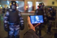 FILE In this file photo taken on Tuesday, Feb. 2, 2021, A journalist watches a live stream of a court hearings with the Russian opposition leader Alexei Navalny on a screen as Russian Rosguardia (National Guard) soldiers guard in front of the court in Moscow, Russia. The January protests in scores of cities across the sprawling country were the largest outpouring of discontent in years and appeared to have rattled the Kremlin. Police reportedly arrested about 10,000 people in the protests and many demonstrators were beaten, while state media sought to downplay the scale of the protests. (AP Photo/Pavel Golovkin, File)