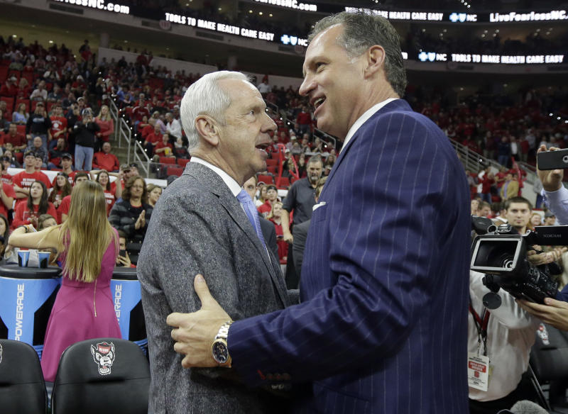 North Carolina coach Roy Williams, left, speaks with North Carolina State coach Mark Gottfried prior to an NCAA college basketball game in Raleigh, N.C., Wednesday, Feb. 15, 2017. (AP Photo/Gerry Broome)