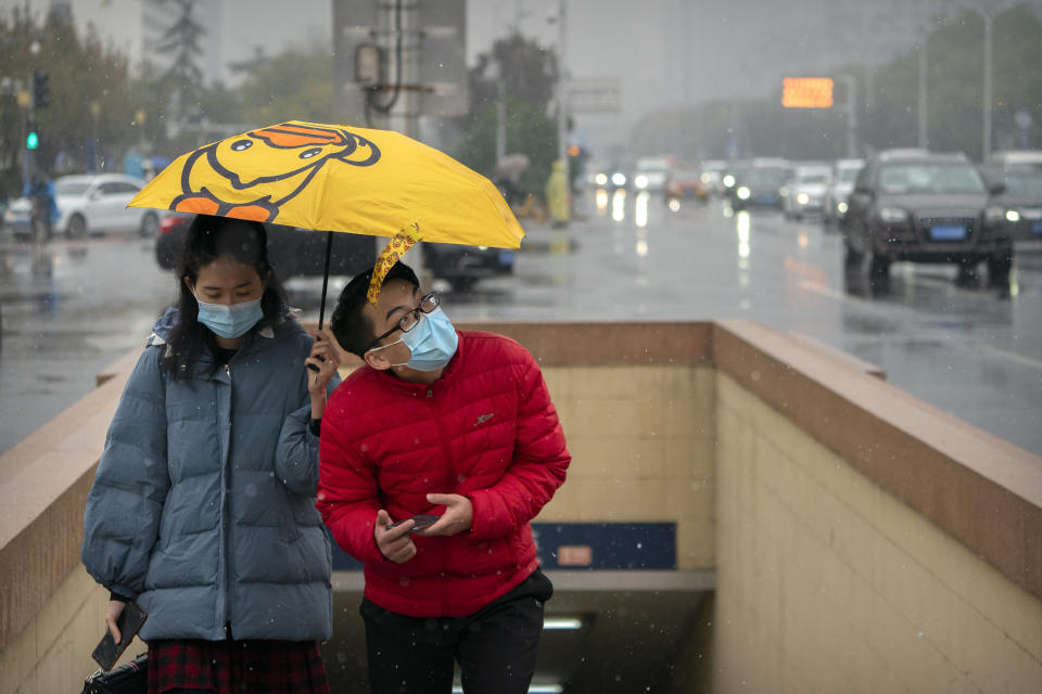 People wearing face masks to protect against the coronavirus hold an umbrella as they walk through the first snowfall of the season in Beijing, Saturday, Nov. 21, 2020. China is starting mass testing on 3 million people in a section of the northern city of Tianjin and has tested thousands of others in a hospital in Shanghai after the discovery of a pair of cases there. (AP Photo/Mark Schiefelbein)