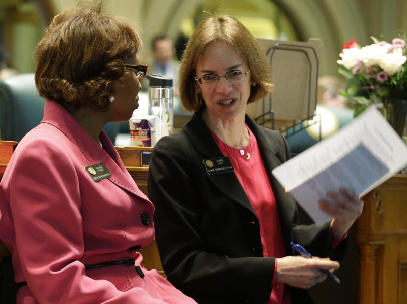 Rep. Rhonda Fields, D-Aurora, left, talks with Rep. Claire Levy, D-Boulder, at the Capitol in Denver on Friday, Feb. 15, 2013. Fields sponsored a bill that would limit the size of ammunition magazines and Levy sponsored a bill dealing with students carrying concealed guns at the universities in the state. Both were being debated on the House floor on Friday.(AP Photo/Ed Andrieski)