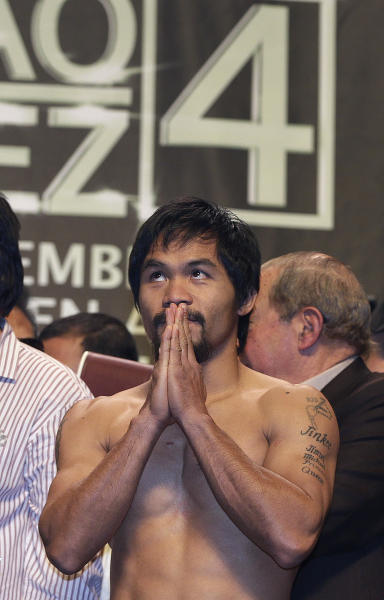 Manny Pacquiao reacts after weighing in for Saturday's welterweight boxing match against Juan Manuel Marquez, Friday, Dec. 7, 2012, in Las Vegas. (AP Photo/Julie Jacobson)
