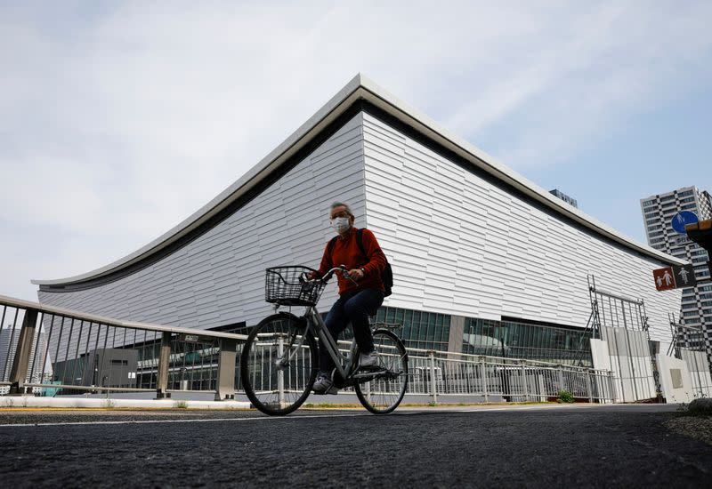 A man wearing a protective mask amid the coronavirus disease (COVID-19) outbreak, cycles past Ariake Arena in Tokyo