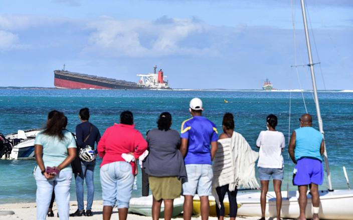 People look at MV Wakashio bulk carrier that had run aground and from which oil is leaking near Blue bay Marine Park in southeast Mauritius on August 6, 2020. - L'Express Maurice/AFP via Getty Images
