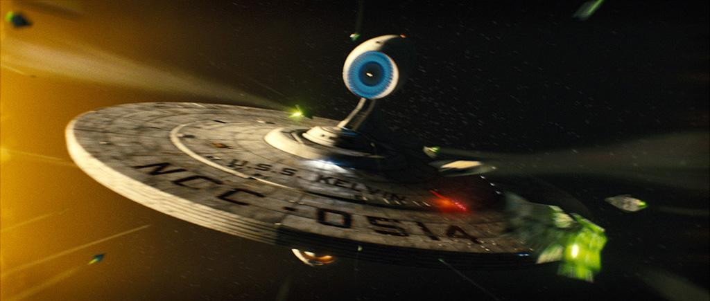 """This first exclusive photo shows the starship USS Kelvin in flight. Kurtzman and Orci couldn't answer if the ship predates the Enterprise or if any characters we already know are aboard. They did say that it was very important to them that the ship designs did not """"stray too far"""" from those in the original show. Orci called the spaceships from the series """"lovely works of art,"""" and they agreed that completely reworking the look without retaining the classic style would be an """"affront to the fans."""""""