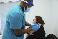 Nurse Andre McFarlane administers a dose of the Moderna Covid-19 vaccine to Teresa Jimenez at the vaccination facility in the Bathgate Post Office on Sunday, Jan. 10, 2021, in the Bronx, New York. The facility, which had been used as a COVID-19 testing site, is part of the city's transition to widespread vaccinations. (AP Photo/Kevin Hagen).