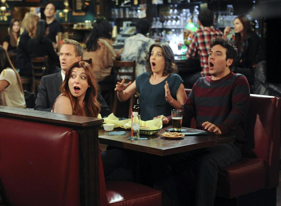 """This image released by CBS shows, clockwise from foreground left, Alyson Hannigan, Neal Patrick Harris, Cobie Smulders and Josh Radnor in a scene from """"How I Met Your Mother."""" Producers filmed the climactic scene of CBS' """"How I Met Your Mother"""" finale eight years ago for fears that the actors involved would become unrecognizable, and have kept it under wraps ever since. The Monday night comedy concludes after nine seasons on March 31 with a one-hour episode. (AP Photo/CBS, Ron P. Jaffe)"""