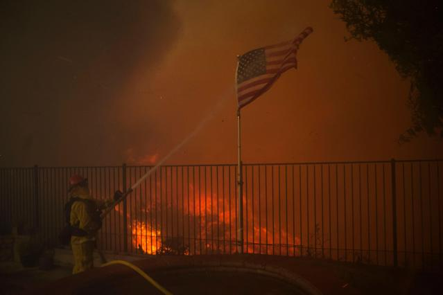 <p>A firefighter hoses down an American flag as flame reach the backyard of a home during the Holy Fire in Lake Elsinore, Calif., Aug. 9, 2018. (Photo: David McNew/EPA-EFE/REX/Shutterstock) </p>