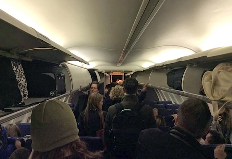 In this Sunday, Jan. 12, 2014 photo provided by Scott Schieffer, passengers gather belongings as they exit a Southwest Airlines flight that was supposed to land at Branson Airport in Branson, Mo., but instead landed at Taney County Airport, in Hollister, Mo., that only has about half as much runway. A Southwest spokesman said all 124 passengers and five crew members were safe. (AP Photo/ Scott Schieffer) MANDATORY CREDIT
