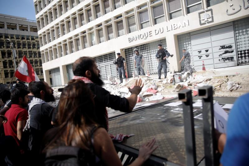 Police officers stand guard as protesters knocked down the fencing as they demonstrate outside of Lebanon Central Bank during ongoing anti-government protests in Beirut