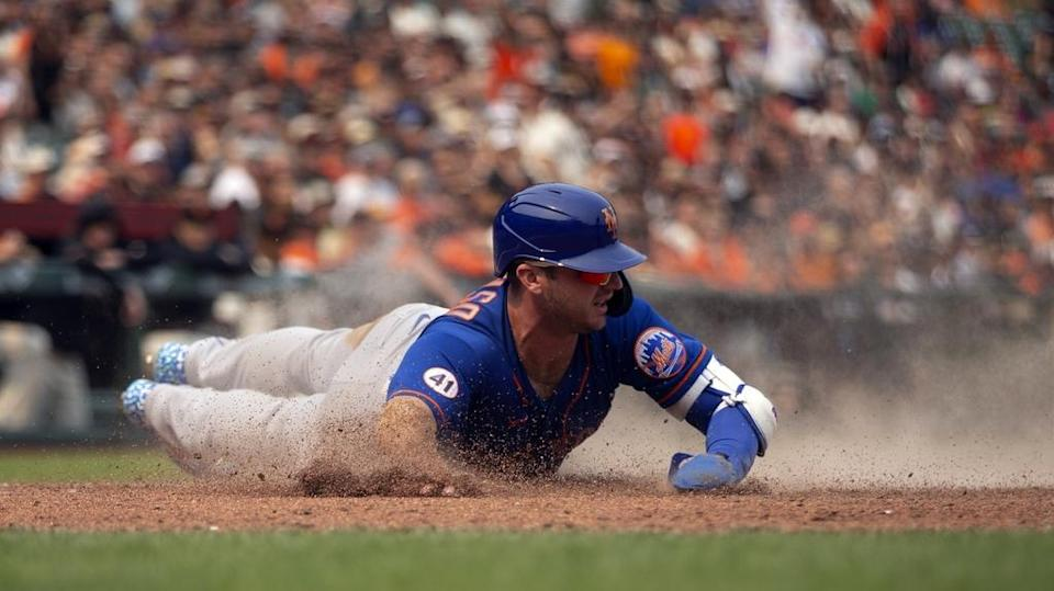 New York Mets first baseman Pete Alonso (20) slides safely home with the tying run on a sacrifice fly by third baseman J.D. Davis (28) during the ninth inning against the San Francisco Giants at Oracle Park.