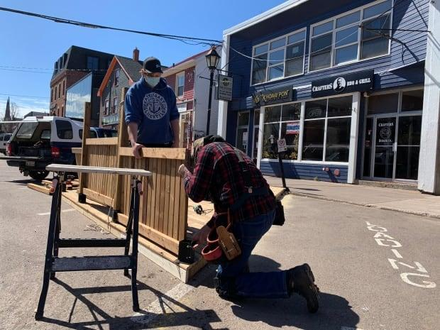 Jim Edwards and his grandson, Alex Wheeler, construct a patio in front of Khoaw Pon and Crafters Bar & Grill in Charlottetown on Saturday. (Shane Ross/CBC - image credit)
