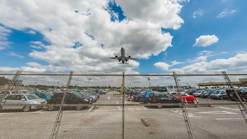 Boeing 777 overflying car park at Heathrow Airport London