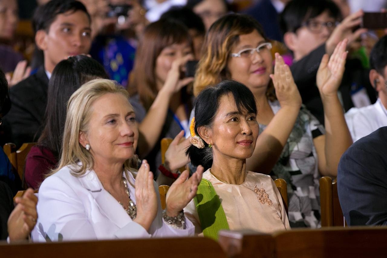 YANGON, MYANMAR - NOVEMBER 19:  US Secretary of State Hilary Clinton (L) listens alongside Aung San Suu Kyi as US President Barack Obama speaks at the University of Yangon during his historical first visit to the country on November 19, 2012 in Yangon, Myanmar. Obama is the first US President to visit Myanmar while on a four-day tour of Southeast Asia that also includes Thailand and Cambodia. (Photo by Paula Bronstein/Getty Images)