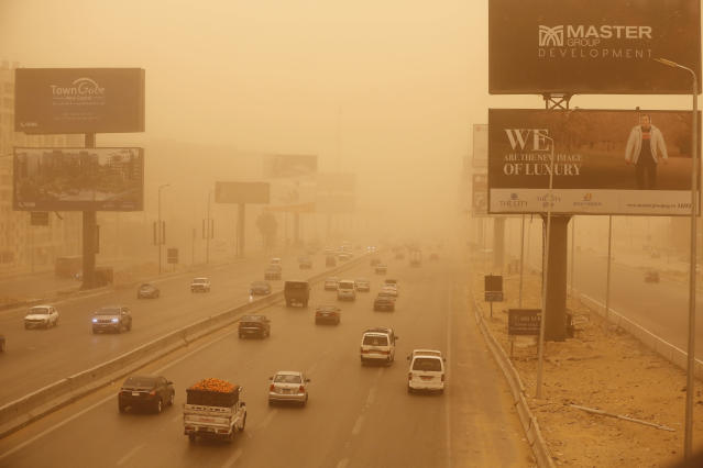 Vehicles drive during a sandstorm in Cairo, Egypt, Wednesday, Jan. 16, 2019. A harsh weather front brought sandstorms, hail and rain to parts of the Middle East, with visibility down in the Egyptian capital as an orange cloud of dust blocked out the sky. (AP Photo/Amr Nabil)