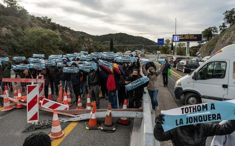 Protesters hold banners as they crowd onto the highway - Credit: David Ramos/Getty Images