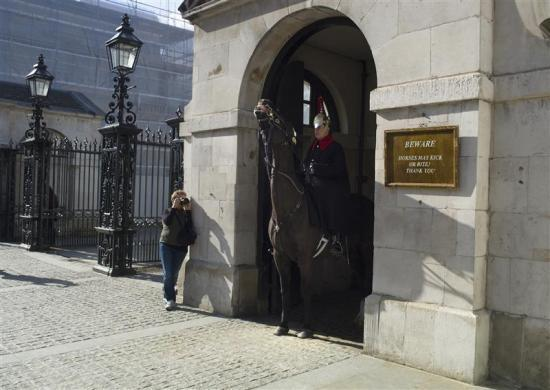 A tourist photographs a member of the Queen's Guard on horseback at the entrance to Horse Guards Parade in London March 8, 2012.