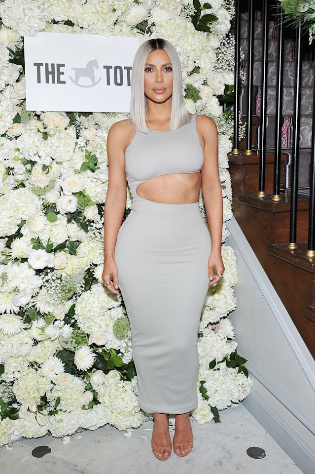 <p>Kim K looked chic in a grey, cut-out dress at The Tot holiday pop-up celebration.<em> [Photo: Getty]</em> </p>