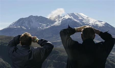 Visitors look up at Mount St Helens venting steam from crater.