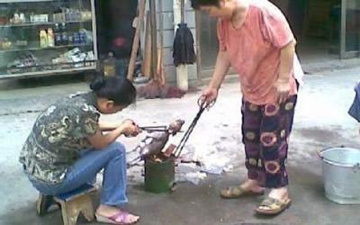 Two women seen roasting the puppy using what looks like a portable stove. (Screengrab from ww.chinasmack.com)