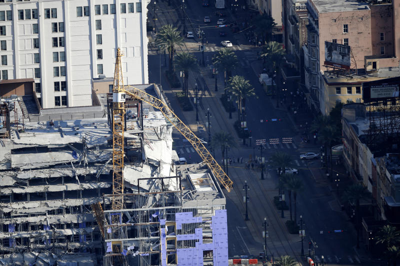 One of two large cranes from the Hard Rock Hotel construction collapse is seen hanging over the edge above Canal Street in this aerial photo, after being detonated for implosion in New Orleans, Sunday, Oct. 20, 2019. (AP Photo/Gerald Herbert)