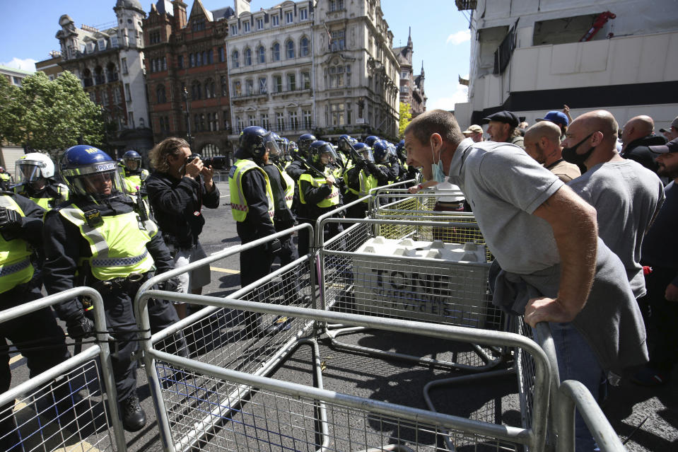 Police are confronted by protesters in Whitehall near Parliament Square, London, during a protest by the Democratic Football Lads Alliance against a Black Lives Matter protest, Saturday June 13, 2020.  The death of George Floyd in the United States, has prompted demonstrations by far-right groups as well as the Black Lives Matter movement and provoked a wider debate regarding many historical figures and Britain's colonial past. (Jonathan Brady/PA via AP)