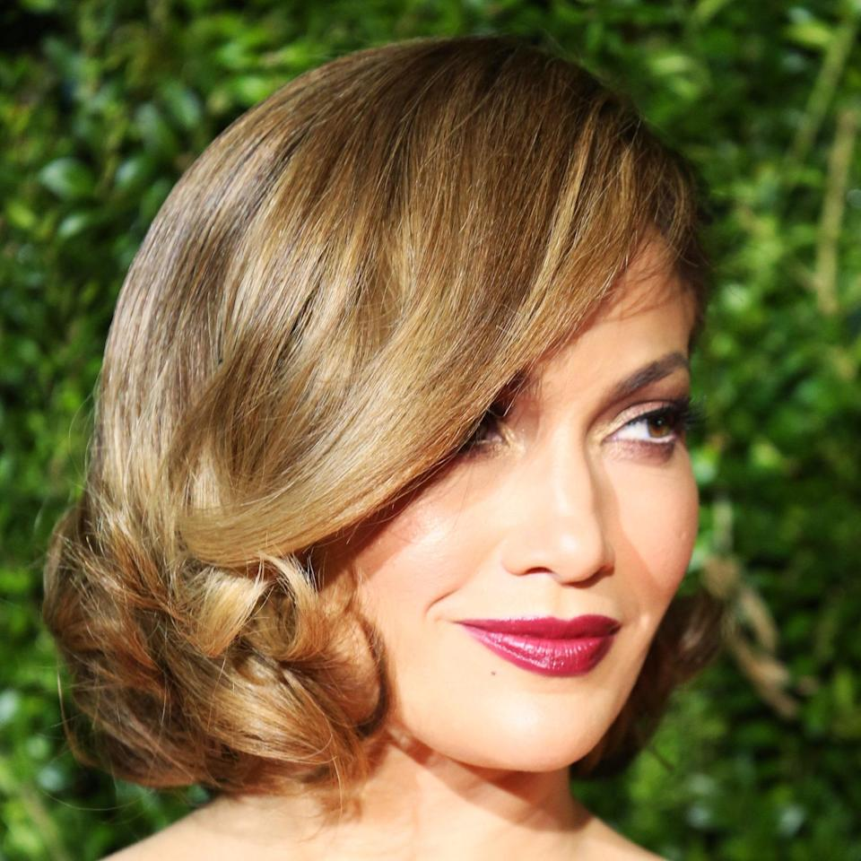 """<p>Jennifer Lopez's hairstyle is a modern take on hairstyles popular in the '50s and '60s, says <a href=""""https://www.instagram.com/sarahpotempa/?hl=en"""" rel=""""nofollow noopener"""" target=""""_blank"""" data-ylk=""""slk:Sarah Potempa"""" class=""""link rapid-noclick-resp"""">Sarah Potempa</a>, hairstylist and founder of <a href=""""https://beachwaver.com/"""" rel=""""nofollow noopener"""" target=""""_blank"""" data-ylk=""""slk:The Beachwaver Co."""" class=""""link rapid-noclick-resp"""">The Beachwaver Co.</a> """"It's cut nice and clean on the bottom [which gives it] a great silhouette and shape"""" Another benefit? """"It brings a lot of attention up to the eyes because of a sweeping bang and strong part.""""</p> <p>If you're deciding what to wear with this, avoid anything with a high neck that may overwhelm your hairstyle.</p>"""